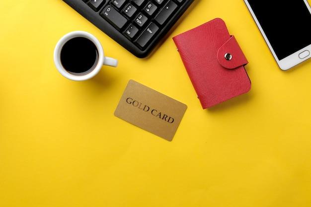 Il concetto di acquisto online. composizione con carta sconto e telefono su sfondo giallo