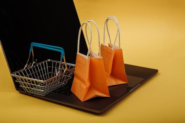 Concetto di shopping online. sacchetti arancioni e carrello della spesa sul computer portatile