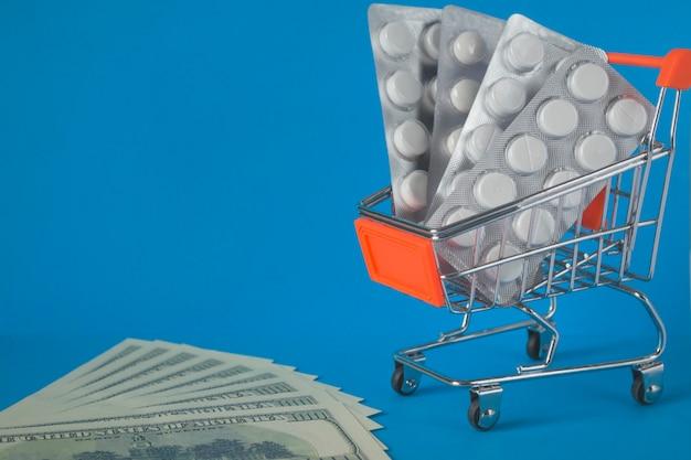 Concetto di shopping online, ordinazione e consegna di medicinali. blister di medicinali in un carrello della spesa su sfondo blu