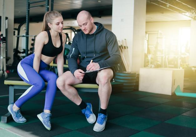 Il concetto di formazione personale. note dell'istruttore nei risultati del taccuino che addestrano donna bionda sportiva che si siede su una panchina. coppia sorridente di sport