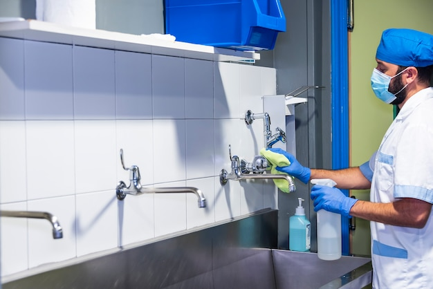 Foto di concetto di un lavoratore dell'ospedale che fa pulizia nella sala operatoria