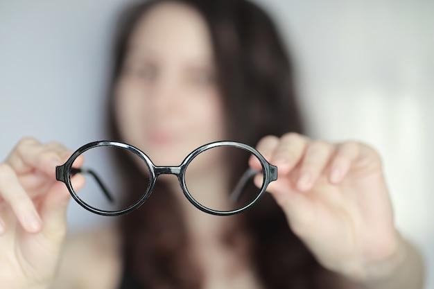 Il concetto di scarsa visione. tieni in mano una lente a contatto e degli occhiali. un poster per la pubblicità di occhiali e lenti.