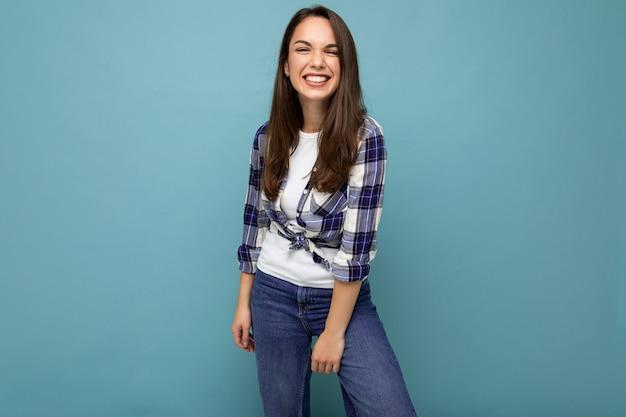 Concetto ritratto di giovane bella donna bruna hipster sorridente in camicia blu e bianca alla moda e