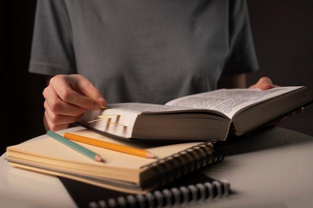 Concetto di preparazione per l'esame, l'apprendimento, lo studio e l'istruzione durante la notte a tavola con cancelleria.