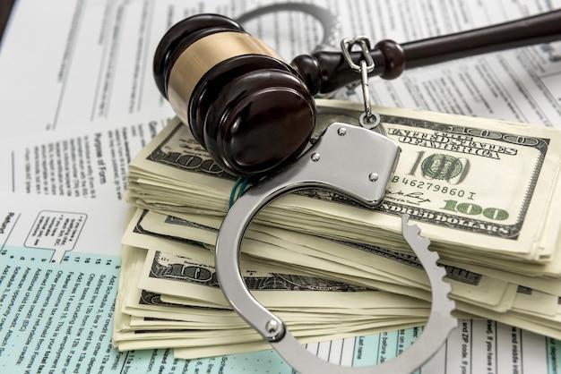 Il concetto di problemi con la legge. le manette della polizia con le manette si trovano sul modulo fiscale usa 1040
