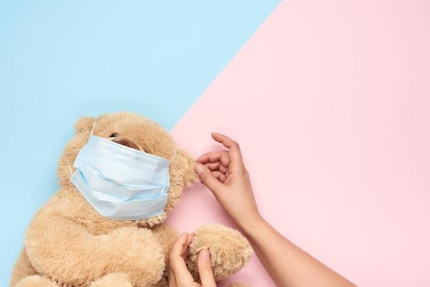 Concetto di protezione dalle malattie respiratorie con orsacchiotto in maschere mediche