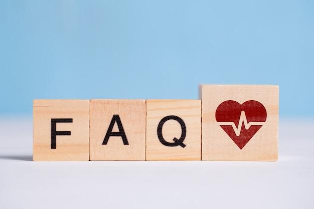 Il concetto di domande e risposte sul trattamento del cuore - faq. il segno sul cubo di legno accanto alle lettere.