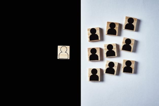 Concetto di razzismo e incomprensione tra persone, pregiudizio e discriminazione. blocco di legno con figure di bianchi e uno con uomo nero
