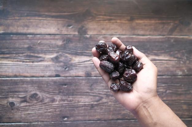 Il concetto della mano del ramadan che tiene i frutti della data