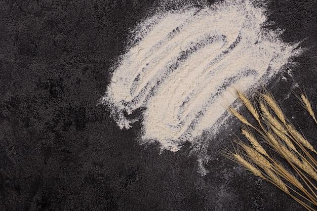 Il concetto di una ricetta su uno sfondo scuro cosparso di farina di frumento