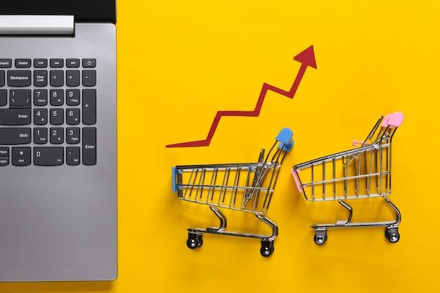 Il concetto di aumento delle vendite. affari online. computer portatile, carrello della spesa con freccia di crescita su un giallo