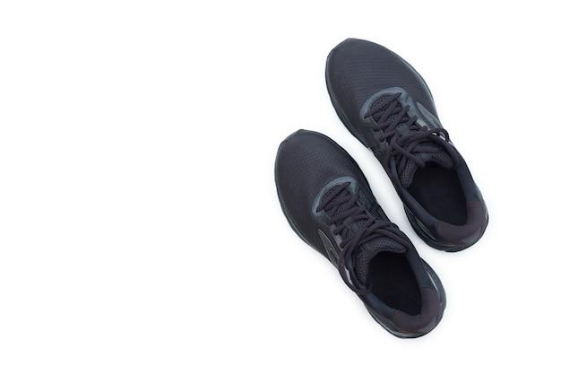 Esecuzione del concetto. scarpe da ginnastica in esecuzione nere su sfondo bianco. vista dall'alto
