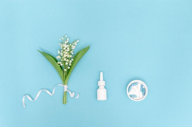 Concetto di allergie stagionali primaverili ed estive alla fioritura. spray nasale bianco e pillole, fiori profumati