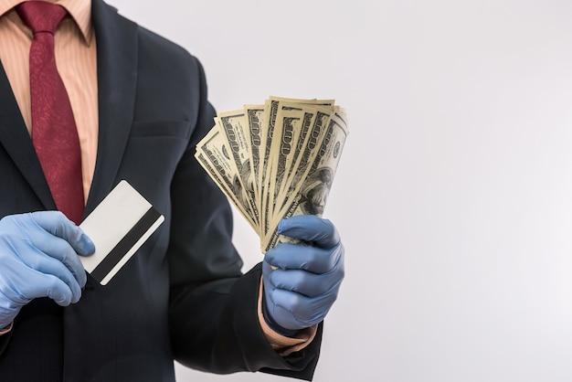 Concetto di sicurezza quando si paga un prodotto o un servizio, uomo d'affari che tiene denaro e carta di credito nei guanti. covid19 coronavirus