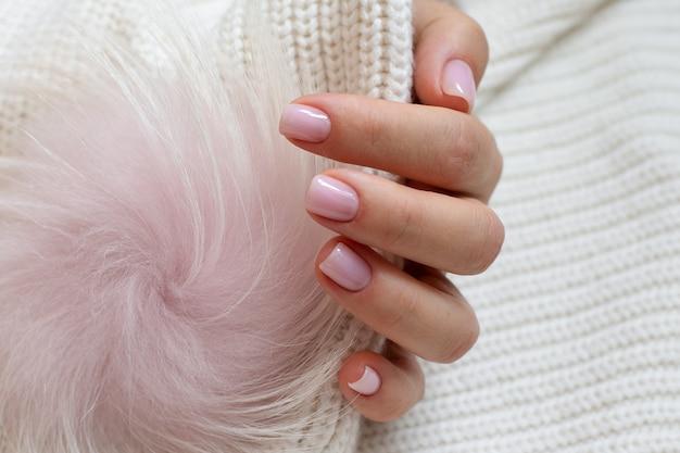 Il concetto di bellezza per la cura personale mani delle donne con una manicure ordinata di colore nudo