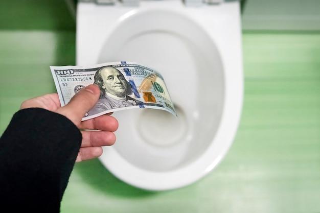 Concetto di insensato spreco di denaro, perdita, spreco inutile, grandi costi dell'acqua, banconote da 100 dollari gettate in un water. perdita di denaro, perdita di denaro