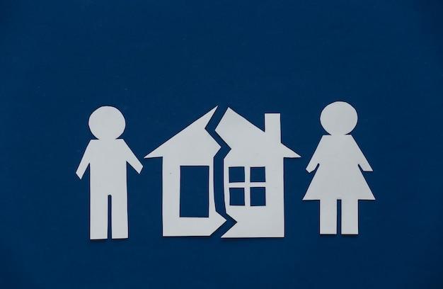 Il concetto di separazione dei beni, divorzio. casa di carta tagliata a metà e figure di uomo e donna su blu classico