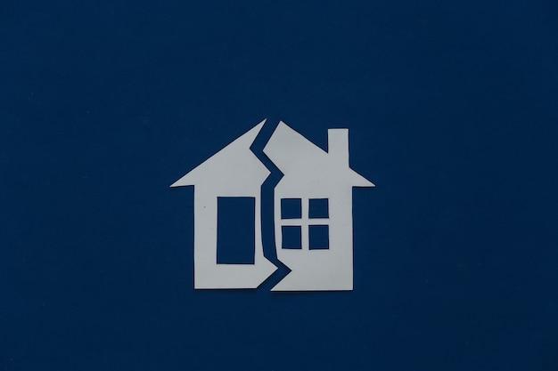 Il concetto di separazione dei beni, divorzio. casa di carta tagliata a metà su un classico blu