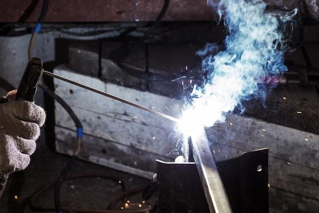 Il concetto di saldatura ad arco in metallo schermato, saldatura a fiamma, costruzione di edifici in strutture metalliche, utilizzo del calore per fondere le parti insieme