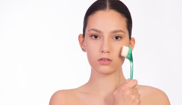 Concetto di cura della pelle, pelle sana e liscia, peeling, trattamento viso. giovane donna con una spazzola per il viso sul viso.