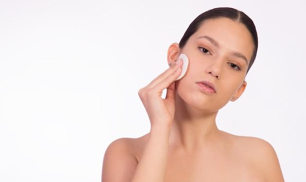 Concetto di pulizia della pelle, rimozione del trucco, pelle pulita e sana. giovane donna che tiene il tampone cosmetico sul viso.