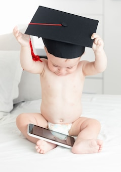 Concetto di bambino intelligente. neonato sveglio in berretto di laurea che naviga in internet su tablet digitale