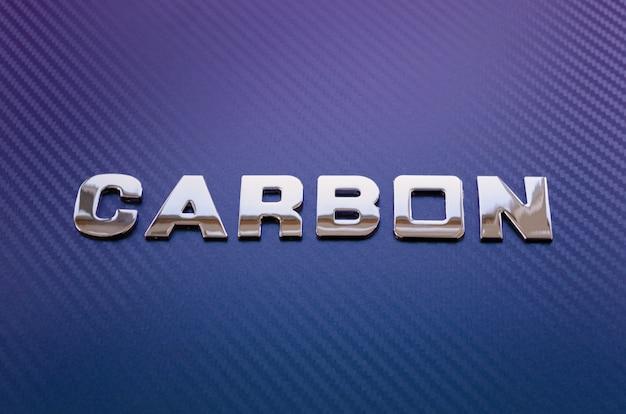 Concetto di sport, velocità, corsa e leggerezza. parola carbonio scritto con lettere cromate sulla superficie in fibra di carbonio viola-blu