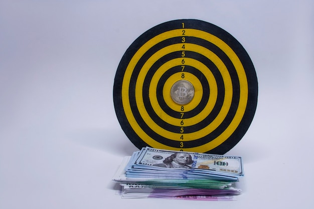 Concetto di successo e raggiungimento degli obiettivi. bersaglio per le freccette rotondo con un fascio di dollari, euro e una moneta bitcoin al centro del cerchio.