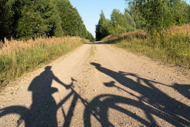 Concetto di un viaggio in bicicletta estivo con ombre di persone in bicicletta sulla strada forestale