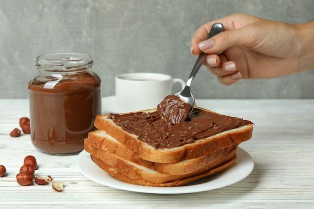 Concetto di gustosa colazione con pasta di cioccolato su tavolo di legno bianco