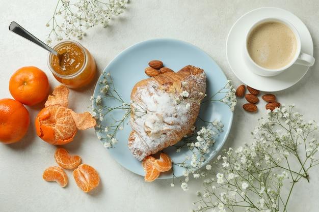 Concetto di gustosa colazione con croissant, marmellata di mandarini e caffè su un tavolo strutturato bianco