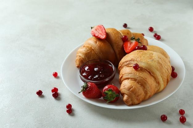 Concetto di gustosa colazione con croissant sulla tabella testurizzata bianca