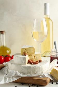 Concetto di gustoso mangiare con camembert, nocciole e vino sul tavolo bianco
