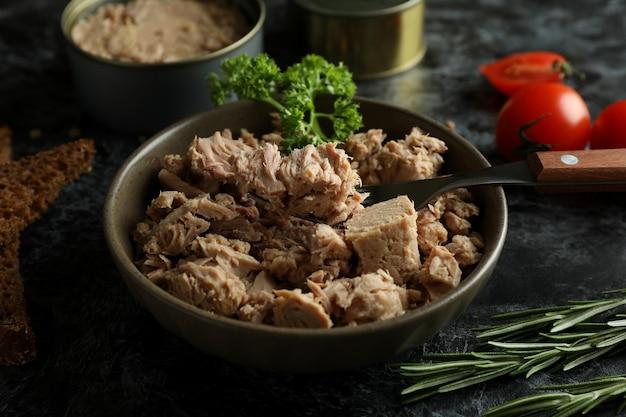 Concetto di mangiare gustoso con tonno in scatola su sfondo nero affumicato