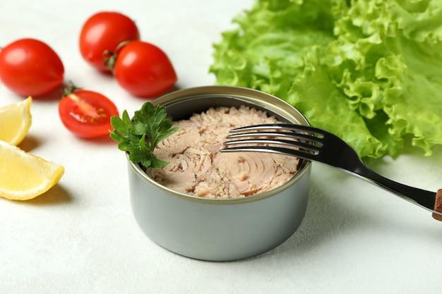Concetto di mangiare gustoso con tonno in scatola su sfondo bianco strutturato