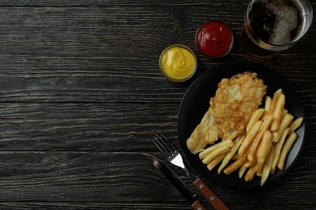 Concetto di gustoso mangiare con patatine fritte e pesce e birra su legno