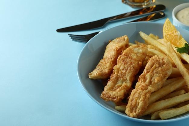Concetto di gustoso mangiare con pesce fritto e patatine fritte e birra sul blu