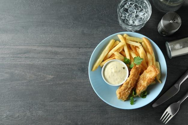Concetto di gustoso mangiare con pesce fritto e patatine fritte sul tavolo con texture scuro