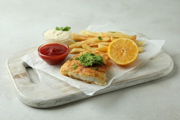 Concetto di gustoso mangiare con pesce fritto e patatine fritte sulla tavola strutturata bianca