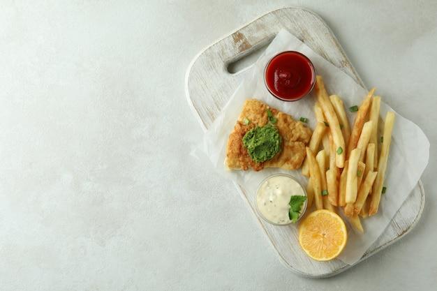 Concetto di gustoso mangiare con pesce fritto e patatine fritte su bianco con texture