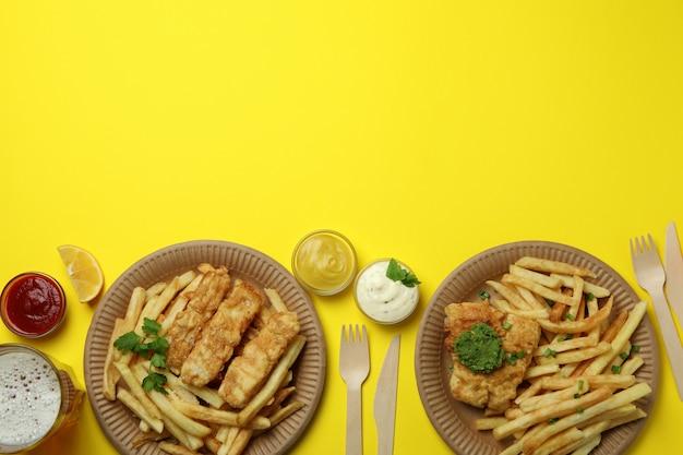 Concetto di gustoso mangiare con pesce fritto e patatine su giallo