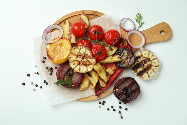 Concetto di gustoso mangiare con verdure grigliate su bianco
