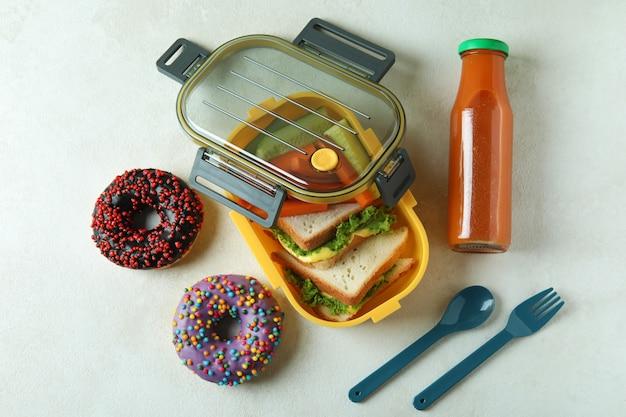 Concetto di mangiare gustoso con il pranzo al sacco sul tavolo strutturato bianco
