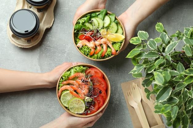 Concetto di mangiare gustoso con insalate di gamberi sul tavolo grigio