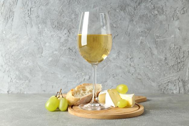 Concetto di mangiare gustoso con vino bianco su un tavolo strutturato grigio