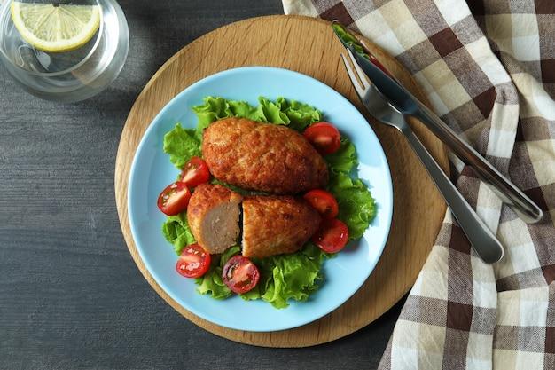 Concetto di cibo gustoso con cotolette sul tavolo di legno scuro