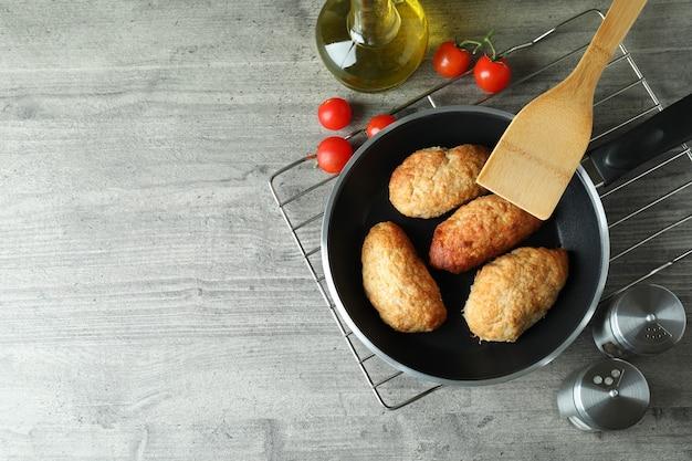 Concetto di cibo gustoso con cotolette sul tavolo strutturato grigio