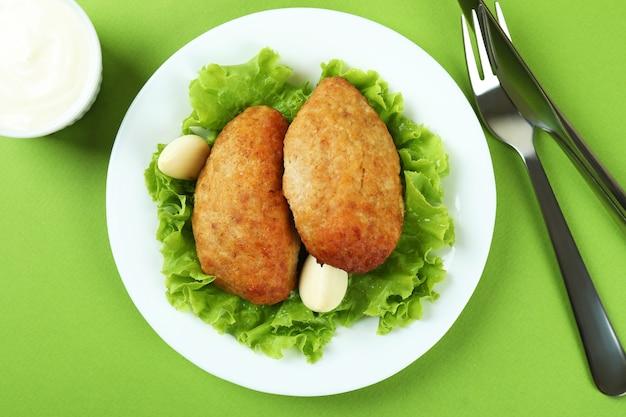Concetto di cibo gustoso con cotolette su sfondo verde