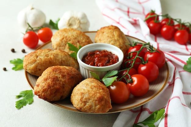 Concetto di cibo gustoso con cotolette su un tavolo strutturato bianco
