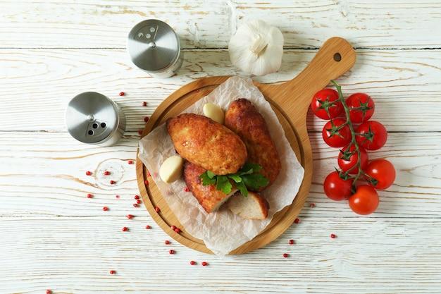 Concetto di cibo gustoso con cotolette sul tavolo di legno bianco